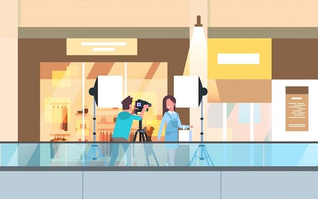 Professionele man fotograaf met dslr camera op statief schieten mooie vrouw model meisje poseren in moderne shoping mall supermarkt binnenlandse horizontale volledige lengte Premium Vector