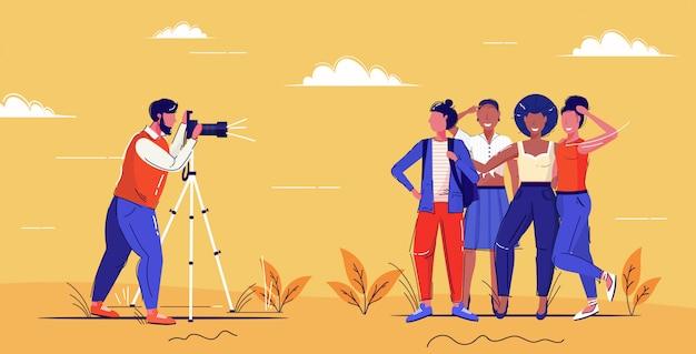 Professionele mannelijke fotograaf met behulp van digitale dslr camera op statief schieten mix race meisjes poseren samen voor foto mode shoot concept volledige lengte schets Premium Vector
