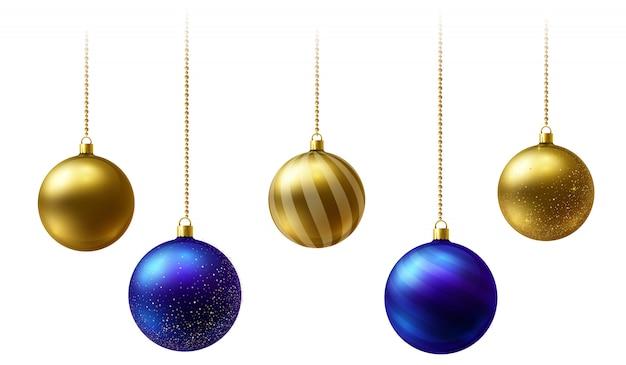 Realistische gouden en blauwe kerstballen die op gouden parelkettingen hangen op witte achtergrond. Premium Vector