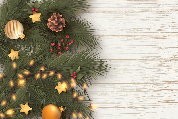 Realistische kerst achtergrond met bladeren en lichten Gratis Vector