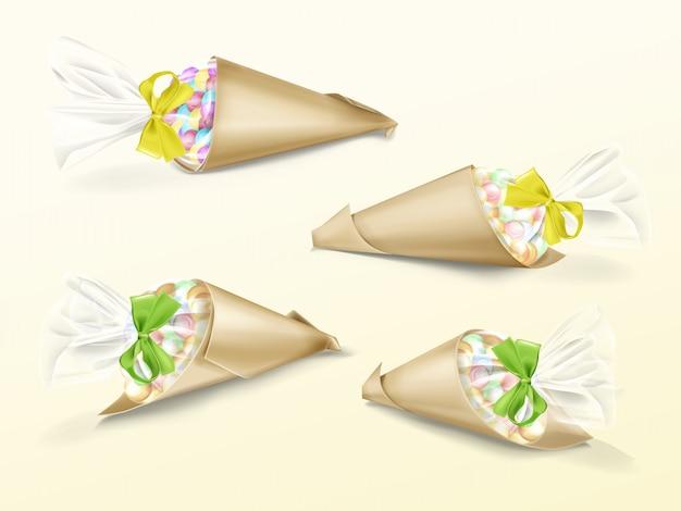 Realistische set van papieren kegelzakken met kleurrijke snoep dragee en gele en groene satijnen lint Gratis Vector