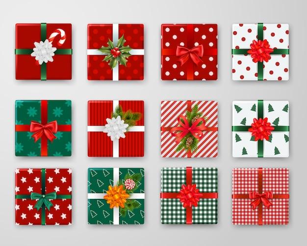 Realistische set van verpakte kerst geschenkdozen met kleurrijke linten en strikken geïsoleerd Gratis Vector