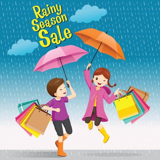 Regenseizoen verkoop, jongen en meisje onder paraplu speels springen met veel boodschappentassen Premium Vector