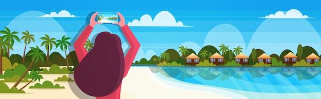 Reisblogger met smartphone camera vrouw op tropisch strand nemen van foto of video bloggen live streaming zomervakantie concept zeegezicht achtergrond horizontaal portret Premium Vector