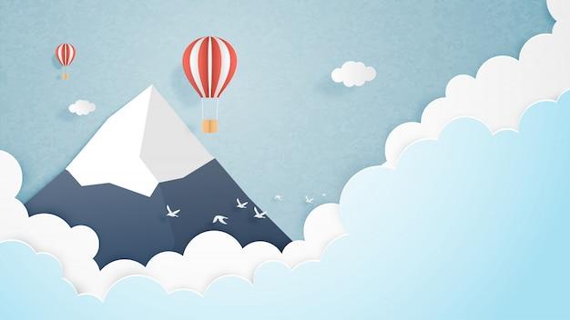 Reizen concept. origami maakte hete luchtballon die over berg met wolken en hemelachtergrond en ruimte vliegt. Premium Vector