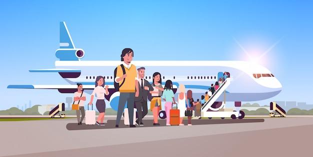 Reizigers met rij die van de bagage de bevindende lijn naar vliegtuigpassagiers gaan die de ladder beklimmen om vliegtuigen in te schepen die reisconcept vlak horizontaal inschepen Premium Vector