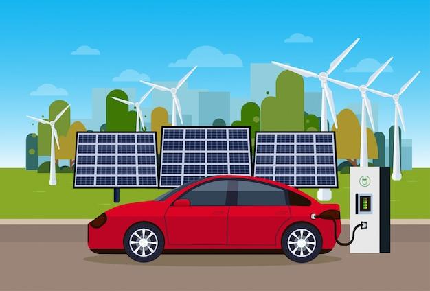 Rode elektrische auto opladen op station van wind trurbines en zonnepaneel batterijen eco vriendelijke vechicle concept Premium Vector