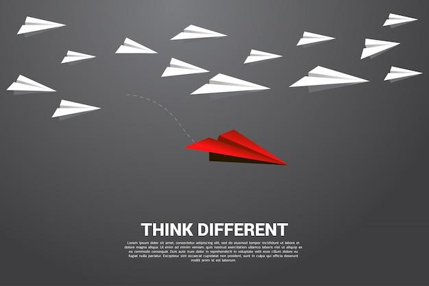 Rood origamidocument vliegtuig dat van groep wit uitgaat. bedrijfsconcept van verstoring en visieopdracht. Premium Vector