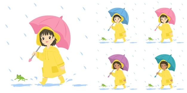 Schattige kinderen in gele regenjas en met een paraplu, set. Premium Vector