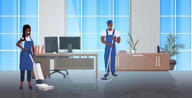 Schoonmakers paar met dweil en stofzuiger afro-amerikaanse conciërges team in uniform samen te werken schoonmaak concept moderne kantoor interieur horizontale volledige lengte Premium Vector