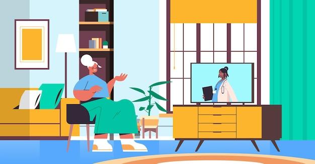 Senior vrouw kijken naar online video overleg met vrouwelijke arts op tv-scherm gezondheidszorg telegeneeskunde medisch advies concept woonkamer interieur horizontaal Premium Vector