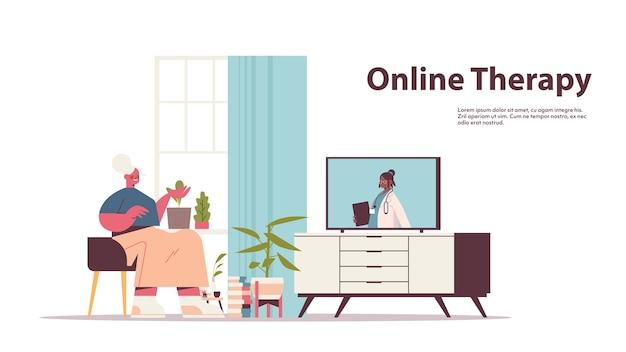 Senior vrouw kijken naar online video overleg met vrouwelijke arts op tv-scherm gezondheidszorg telegeneeskunde medisch advies kopie ruimte Premium Vector