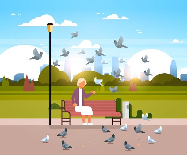 Senior vrouw voedende zwerm duiven Premium Vector