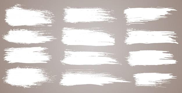 Set van grunge artistieke penseelstreken, borstels. grunge aquarel brede penseelstreken. witte collectie geïsoleerd op een witte achtergrond Premium Vector