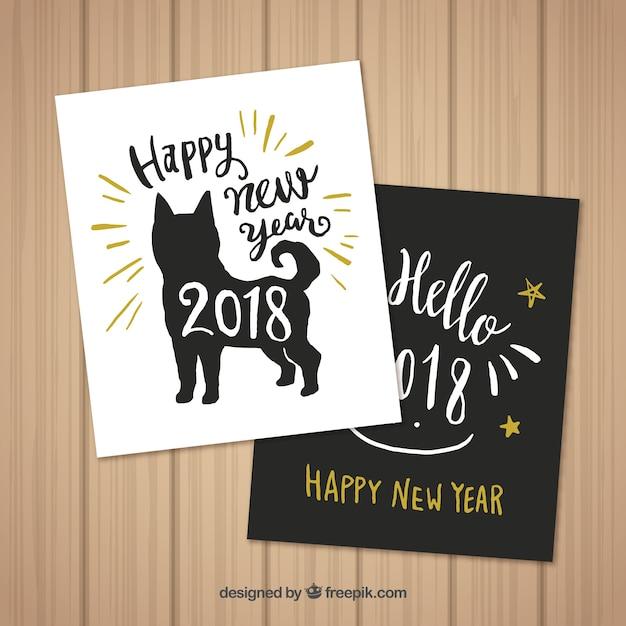 Set van twee hand getrokken kaarten van het nieuwe jaar met een hond Gratis Vector