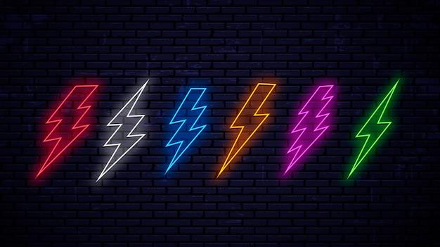 Set van veelkleurige heldere neon bliksemschichten geïsoleerd op muur achtergrond. neon bliksem rood, wit, blauw, geel, roze, groene kleur. Premium Vector