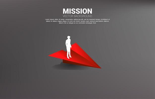 Silhouet die van zakenman zich op rood origamidocument vliegtuig bevinden. businessconcept van leiderschap, startend bedrijf en ondernemer Premium Vector