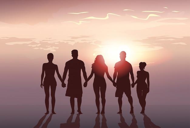 Silhouet mensen groep staan hand in hand man en vrouw volledige lengte op zonsondergang achtergrond Premium Vector