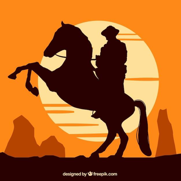 Silhouet van cowboy die bij zonsondergang berijdt Gratis Vector