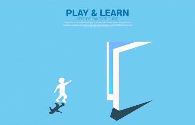 Silhouet van lopende jongen wijs naar deur van open boek. concept van onderwijsoplossing. wereld van kennis. Premium Vector