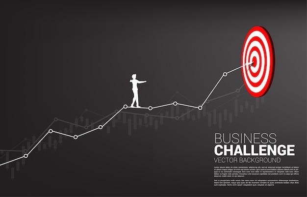 Silhouet van zakenman lopen touw online grafiek naar midden van dartbord. concept van targeting en zakelijke uitdaging. route naar succes. Premium Vector