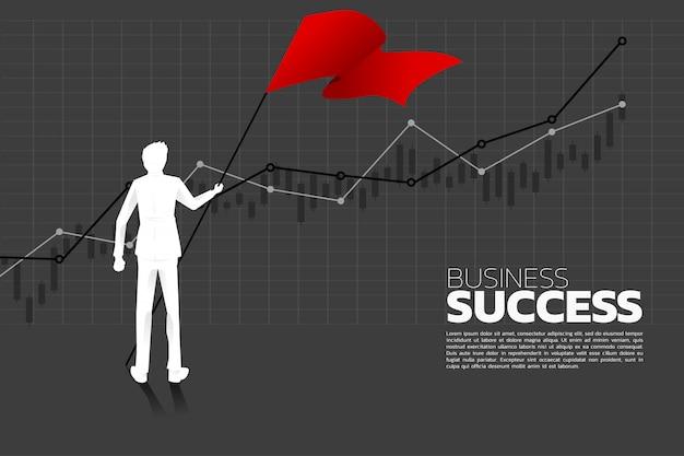 Silhouet van zakenman met de rode vlag die zich met de groeigrafiek bevindt. Premium Vector