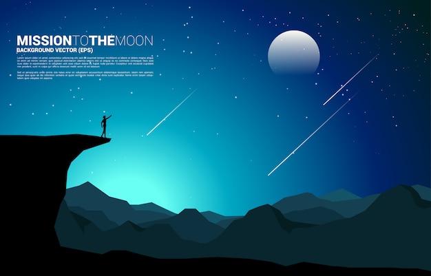 Silhouet van zakenmanpunt vooruit van bergklip naar de maan 's nachts. bedrijfsvisie missie en doel Premium Vector