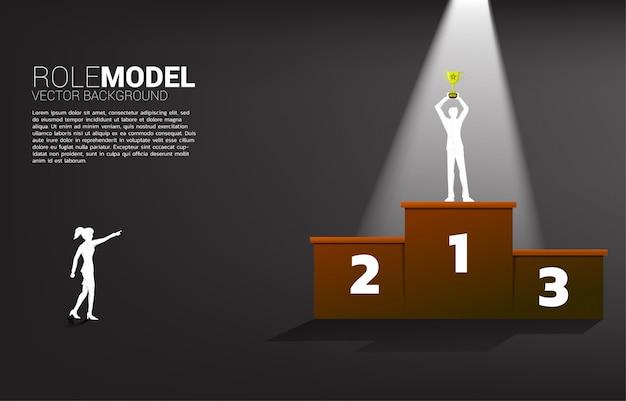 Silhouet zakenvrouw wijsvinger aan zakenman met kampioen trofee op eerste plaats podium. Premium Vector