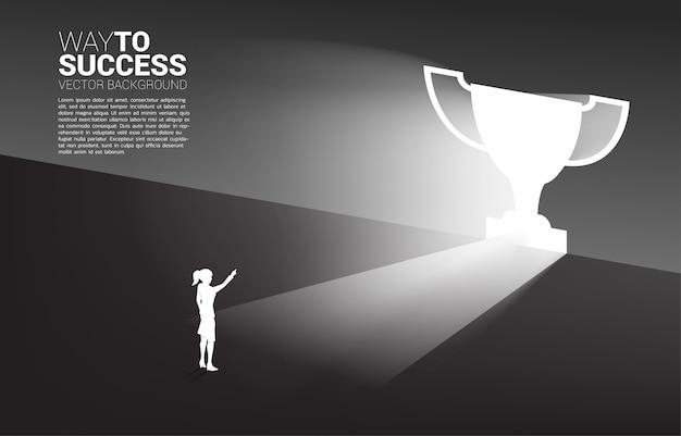Silhouetonderneemster die zich in licht van de vormtrofee van de uitgangsdeur bevinden. businessconcept van route naar winnaar en kampioen Premium Vector