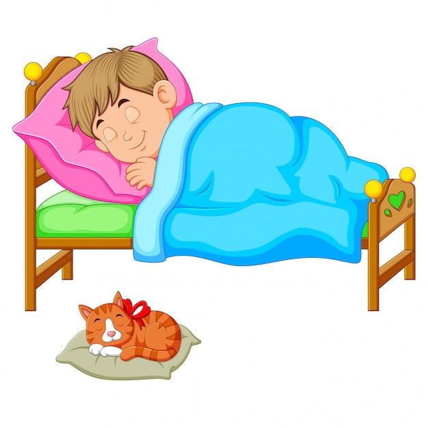 Slaapjongen in bed met een katje Premium Vector