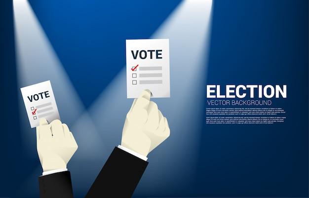 Sluit omhoog zakenmanhand met stembriefje voor verkiezing. Premium Vector
