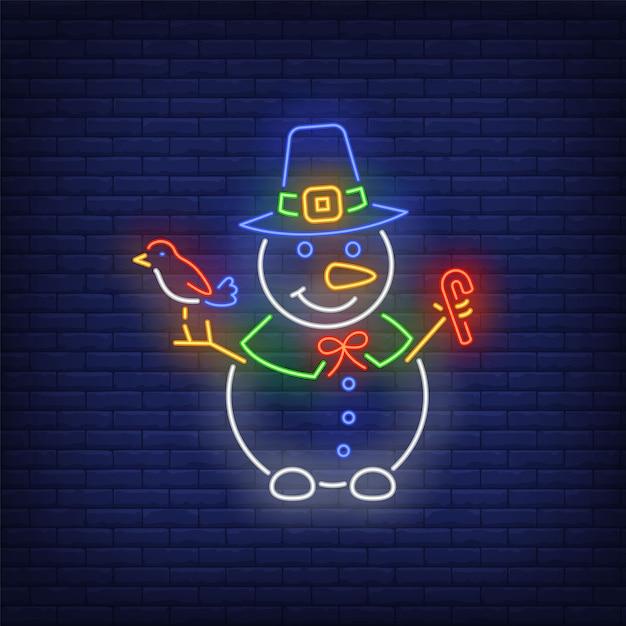 Sneeuwman die heksenhoed draagt, vogel en suikergoedriet in neonstijl houdt Gratis Vector