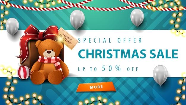Speciale aanbieding, kerstuitverkoop, tot 50% korting, mooie blauwe en witte kortingsbanner met slingers, witte ballonnen, knop en cadeau met teddybeer Premium Vector