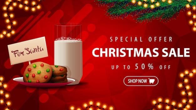 Speciale aanbieding, kerstuitverkoop, tot 50% korting, mooie rode kortingsbanner met kerstboomtakken, slinger en koekjes met een glas melk voor de kerstman Premium Vector