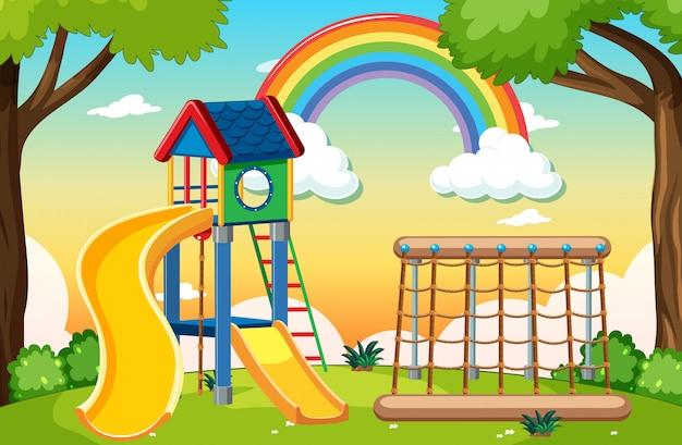 Speeltuin voor kinderen in het park met regenboog aan de hemel overdag cartoon stijl Gratis Vector