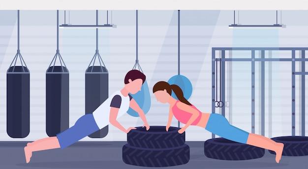 Sport paar doen push-up oefening op banden man vrouw uit te werken samen crossfit training gezonde levensstijl concept moderne sportschool interieur vlak en horizontaal Premium Vector
