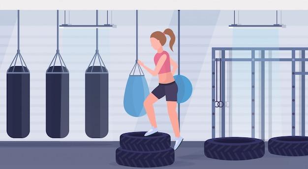 Sportieve vrouw die hurkzit op bandenplatform doen meisje opleiding benen training gezonde levensstijl crossfit concept gym met bokszakken moderne health club interieur horizontale flat Premium Vector