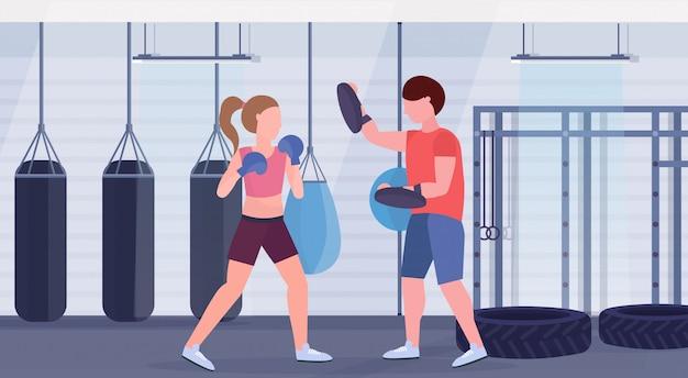 Sportvrouw bokser boksen oefeningen met personal trainer meisje vechter in blauwe handschoenen uitwerken strijd club met bokszakken gym interieur gezonde levensstijl concept Premium Vector