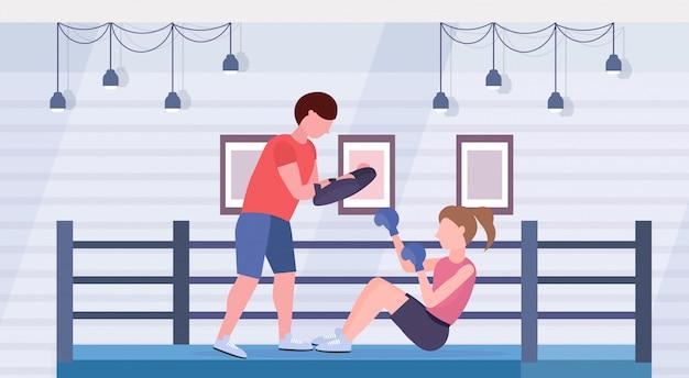 Sportvrouw bokser boksen oefeningen met persoonlijke trainer meisje vechter in blauwe handschoenen uit te werken op vloer strijd club ring arena interieur gezonde levensstijl concept Premium Vector