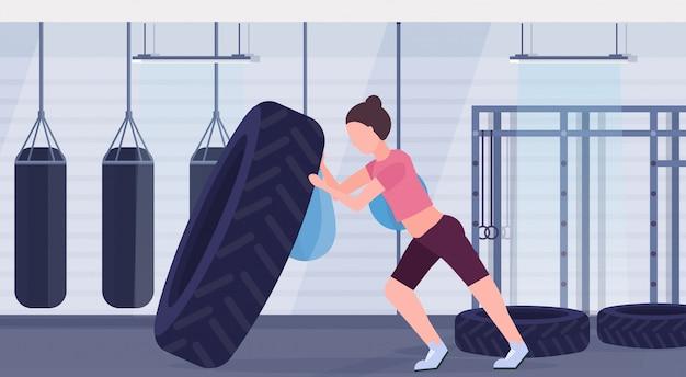 Sportvrouw wegknippen van een band die harde oefeningen doet meisje trainen in de sportschool met bokszakken crossfit training gezonde levensstijl concept moderne health club interieur horizontaal Premium Vector