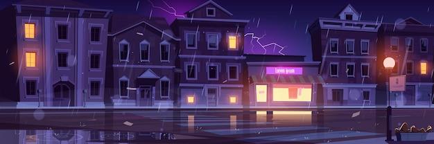Stadsstraat met huizen en lege weg bij koud weer met regen en bliksem. Gratis Vector