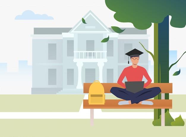 Student die en laptop op bank in campuspark bestudeert gebruikt Gratis Vector
