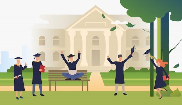Studenten die afstuderen in campuspark vieren Gratis Vector