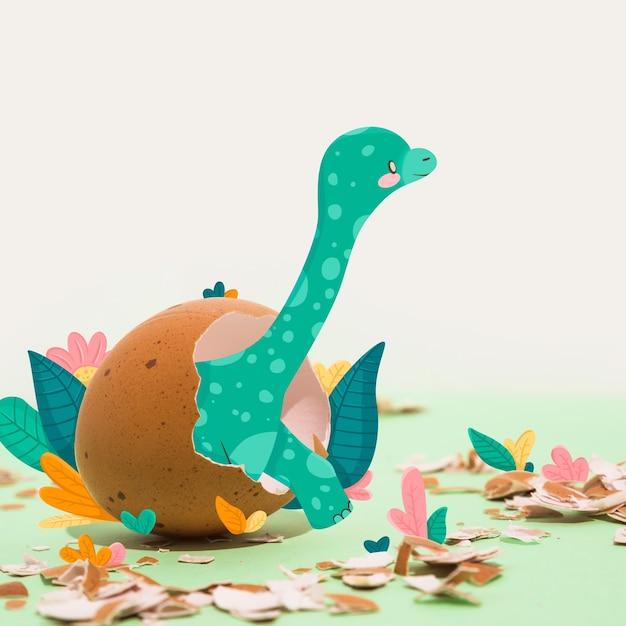 Tekening van een dinosaurus die uit een ei uitbroedt Gratis Vector