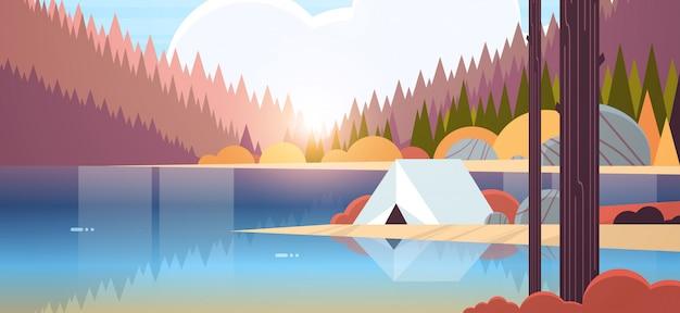 Tent camping gebied in bos camping in de buurt van rivier herfst kamp reizen vakantie concept zonsopgang landschap natuur met water bergen en heuvels Premium Vector