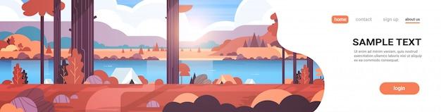 Tenten kampeerterrein in bos herfst kamp concept zonnige dag zonsopgang landschap natuur met water bergen en heuvels Premium Vector