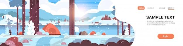 Tenten kampeerterrein in bos winter kamp concept zonnige dag zonsopgang besneeuwde landschap natuur met water bergen en heuvels Premium Vector