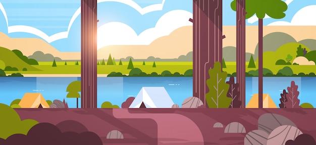 Tenten kampeerterrein in bos zomerkamp zonnige dag zonsopgang landschap natuur met water bergen en heuvels Premium Vector