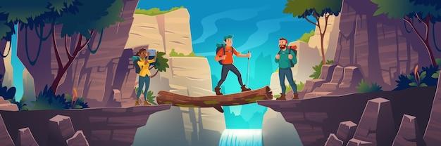 Toeristen steken logboekbrug tussen bergen boven klif in het landschap van rotspieken met waterval en bomen over. het meisje maakt een foto van de natuurweergave van het prachtige landschap. Gratis Vector