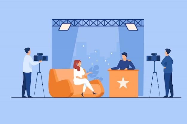 Tv-presentator interviewt een beroemdheid in de studio Gratis Vector
